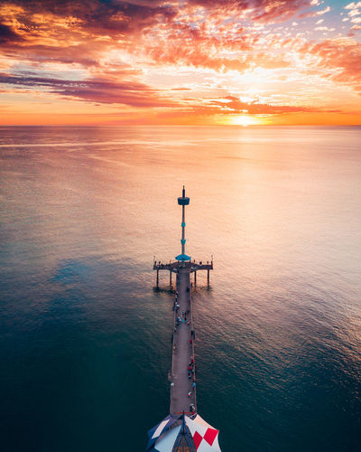 High angle view of people on pier over sea against orange sky
