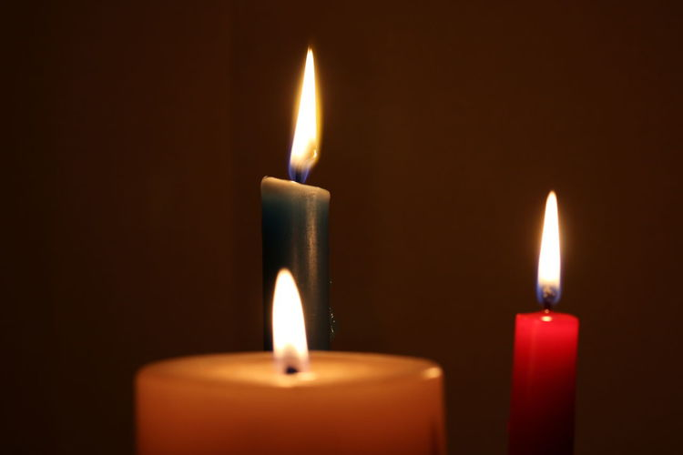 Close-up of lit candles against brown background