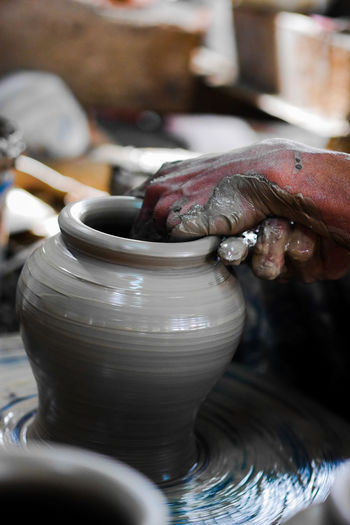 Midsection of man working on pottery wheel