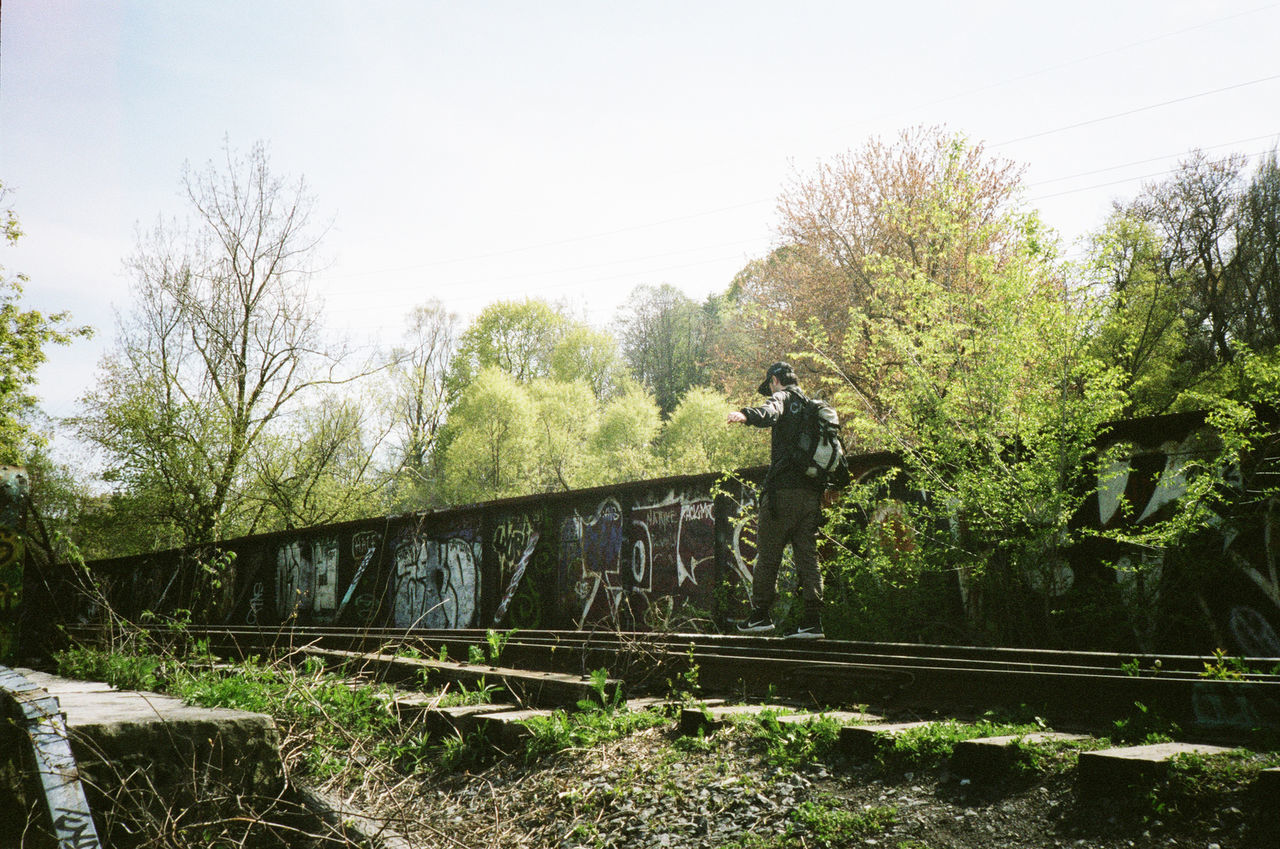 MAN STANDING BY RAILROAD TRACKS AGAINST TREES AND PLANTS