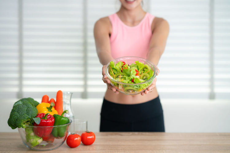 Midsection of woman with healthy food