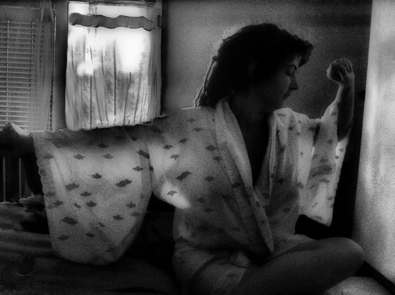 Young woman in robe stretching while sitting on bed