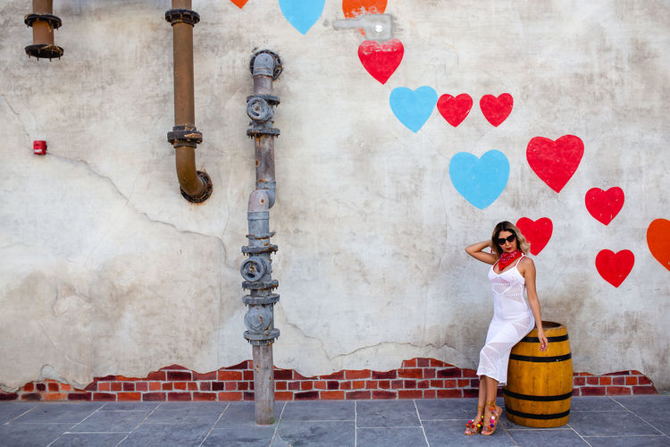 Full length of woman sitting on barrel against artistic wall