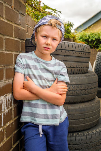 portrait of a boy intyre garage Road Travel Childhood Child One Person Front View Males  Casual Clothing Real People Three Quarter Length Boys Standing Lifestyles Architecture Men Brick Built Structure Day Leisure Activity Brick Wall Innocence Outdoors Tyres Service Underage