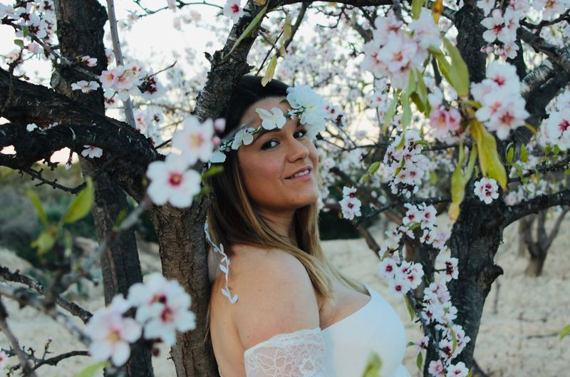 Portrait of bride standing by tree in park