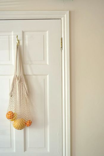 Mesh grocery bag, with variety of citrus inside, hanging on white door at home.