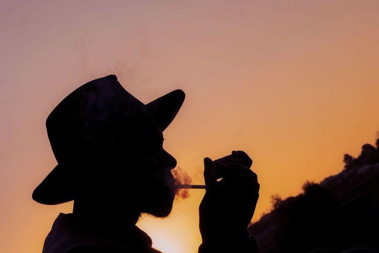 Silhouette man holding orange against sky during sunset