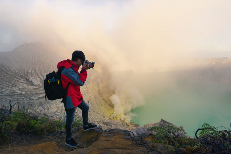 Photographer is shooting picture on top of mountain at sunrise scene., Kawah Ijen volcano. Real People One Person Leisure Activity Full Length Mountain Lifestyles Activity Nature Smoke - Physical Structure Beauty In Nature Standing Fog Photography Themes Travel Rear View Scenics - Nature Men Non-urban Scene Hiking Outdoors Photographer Digital Camera Kawah Ijen Travel Travel Destinations