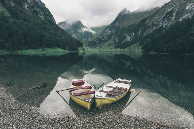 Two paddle boats at the mountain lake on a moody and cloudy day Adventure Boats Explore Fun Lake Landscape Life Live Life Mountain Mountain Lake Mountain Life Outdoors Paddle Paddling Peace And Quiet Peaceful Peaceful View Reflection Swiss Switzerland Travel Destinations Twin Boats Two Boats Two Boats At Lake Water