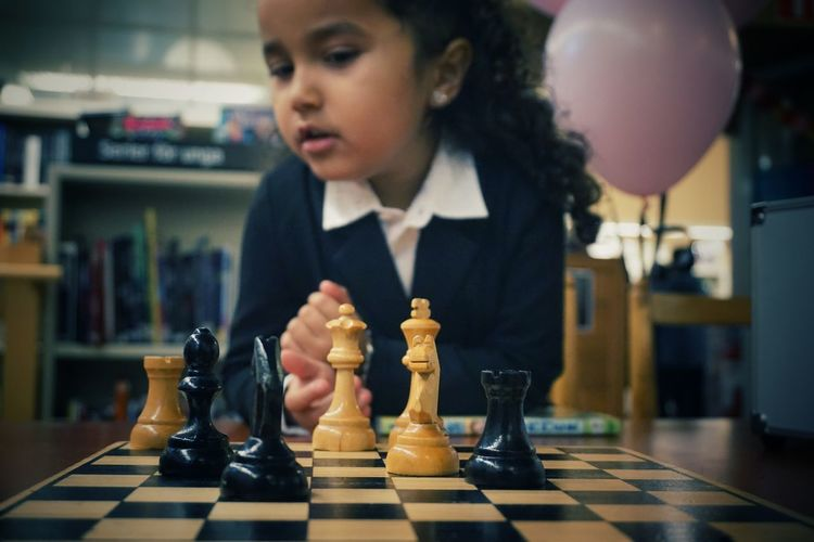 Girl looking away while plying chess on table