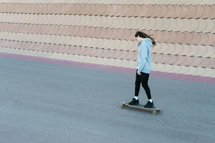 Side view of teenage girl skateboarding on road