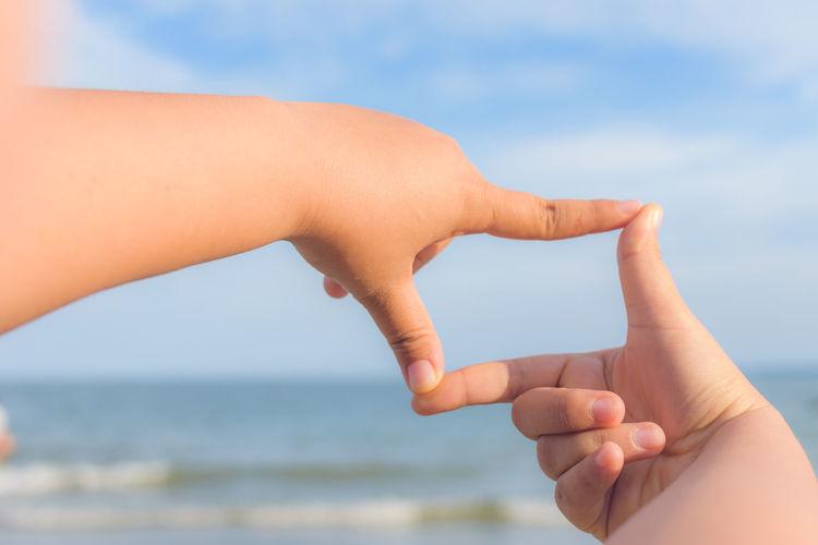 Cropped hands of child making finger frame against sea