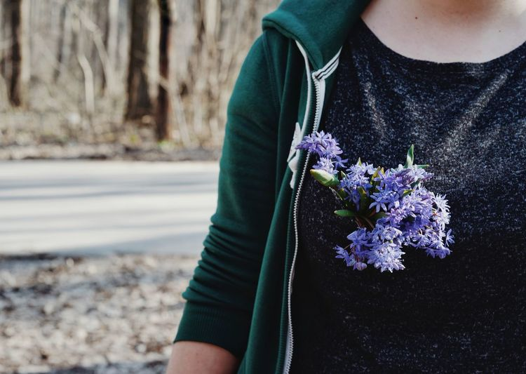 Midsection of woman with purple flowers at roadside