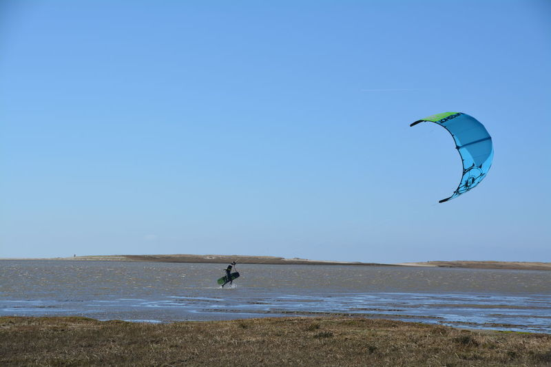 Adventure Beauty In Nature Blue Day Enjoyment Extreme Sports Freedom Fun Kiteboarding Leisure Activity Lifestyles Mid-air Nature Parachute Paragliding Scenics Sky Sport Tranquil Scene Tranquility Unrecognizable Person Vacations Water
