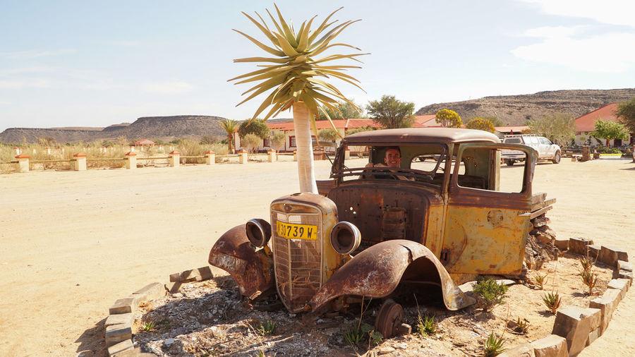 Old abandoned car on land against sky