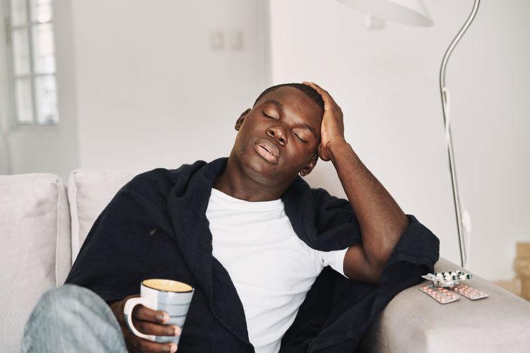 Man holding coffee cup while sleeping on sofa