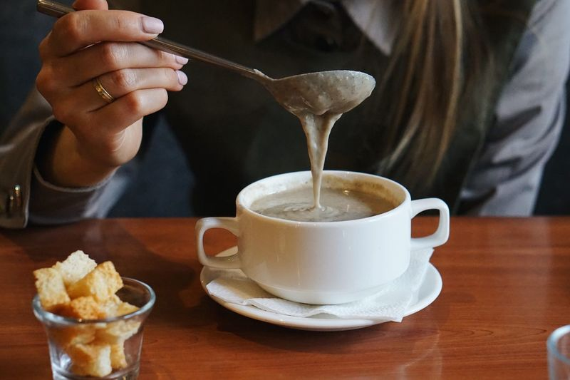 Midsection of woman pouring coffee in cup on table