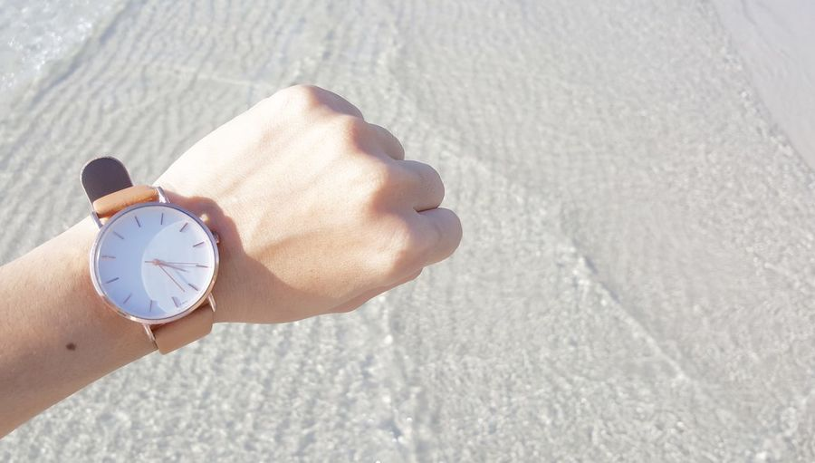 Cropped hand of person showing wristwatch over beach