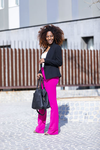 Front view of young beautiful curly woman wearing elegant clothes and handbag while standing in the street in sunny day One Person Curly Hair Full Length Architecture Smiling Young Adult Building Exterior Women Young Women Built Structure Hair Day Hairstyle Real People Bag City Happiness Lifestyles Standing Fashion Beautiful Woman Outdoors Standing Posing Model Handbag  Afro African American Laughing Looking At Camera Looking Away Elegant Attractive Bussinesswoman Empowered City Life Urban Walking Beautiful Pink