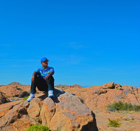 Low angle view of man sitting on rock against clear blue sky