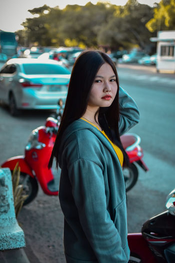Young woman standing on street in city