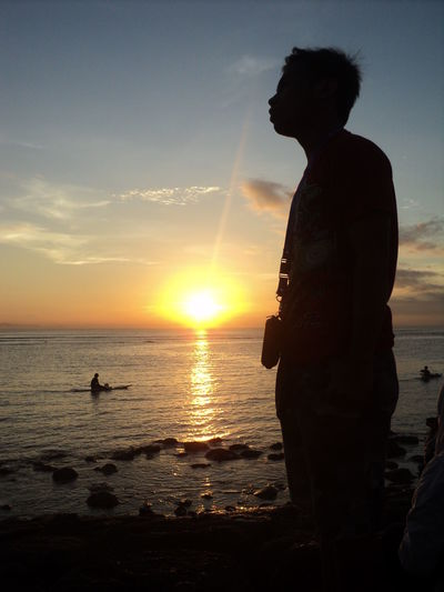 Side view of silhouette man standing at beach against sky during sunset
