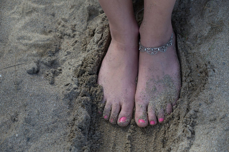 Low section of woman on sand at beach