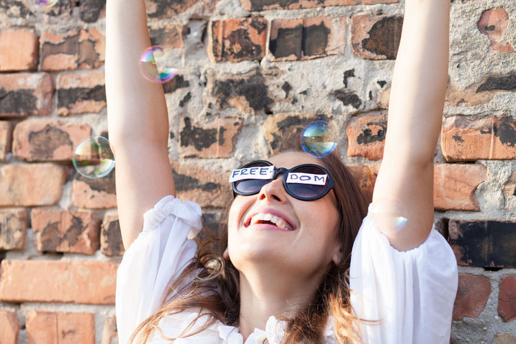 Cheerful woman wearing sunglasses with freedom text while playing with bubbles against brick wall