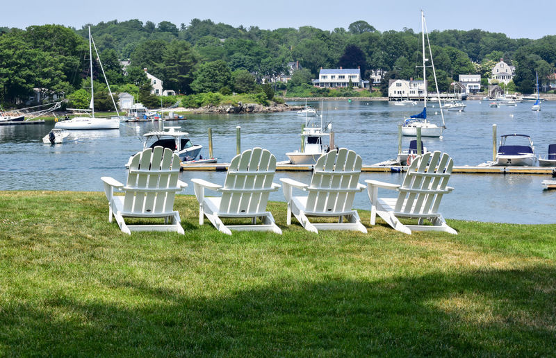 Lawn chairs in Summer on New England Coast New England  Summertime Architecture Backgrounds Beauty In Nature Bradley Olson Bradleywarren Photography Day Grass Green Color In A Row Lake Land Luxury Mode Of Transportation Moored Nature Nautical Vessel No People Outdoors Plant Scenics Seat Summer Tourism Tourist Destination Transportation Tree Water