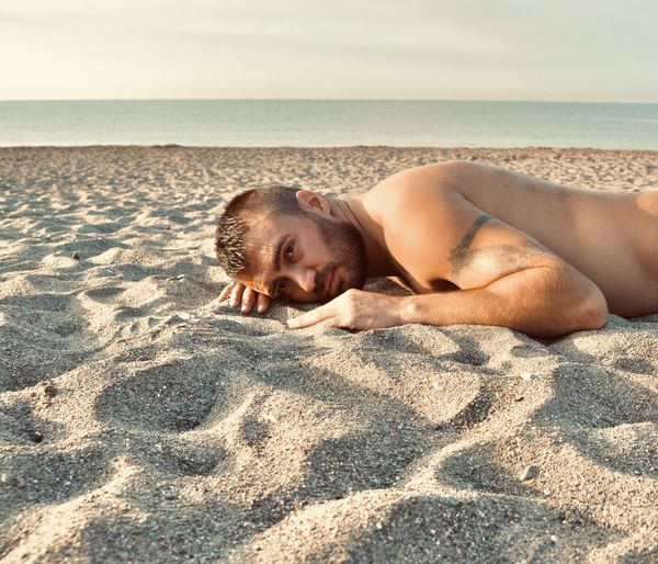 Portrait of shirtless man lying on sand at beach