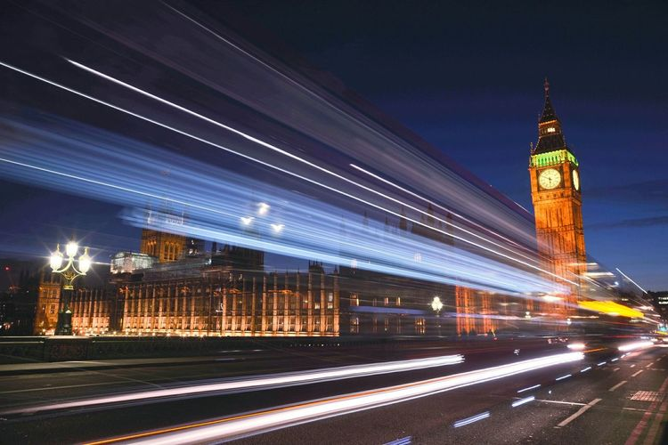 Light trails on road by big ben against sky at night