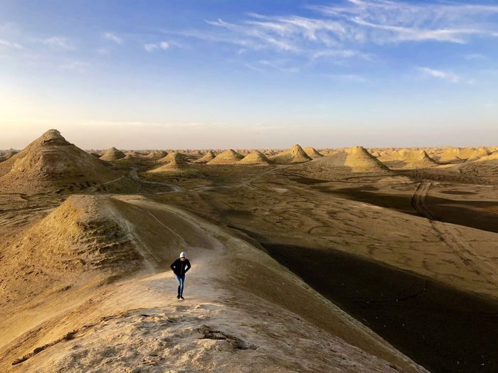High angle view of girl standing at desert against sky