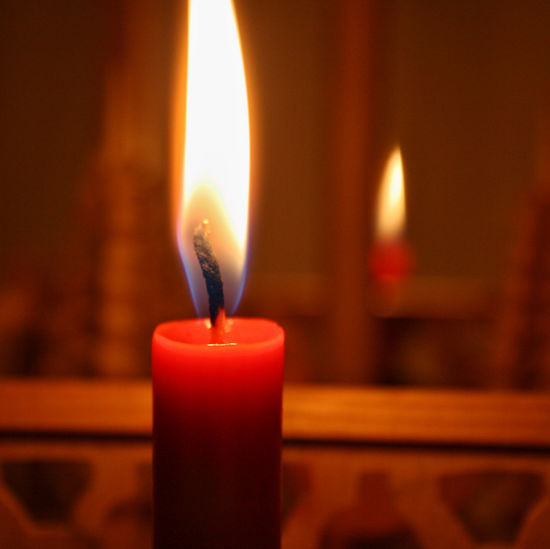 Close-up of lit candle against blurred background