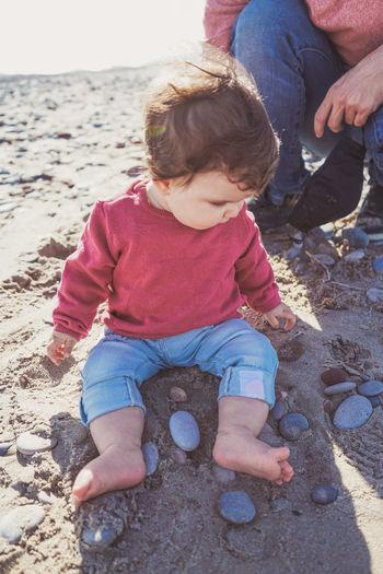 Boy sitting on sand at beach