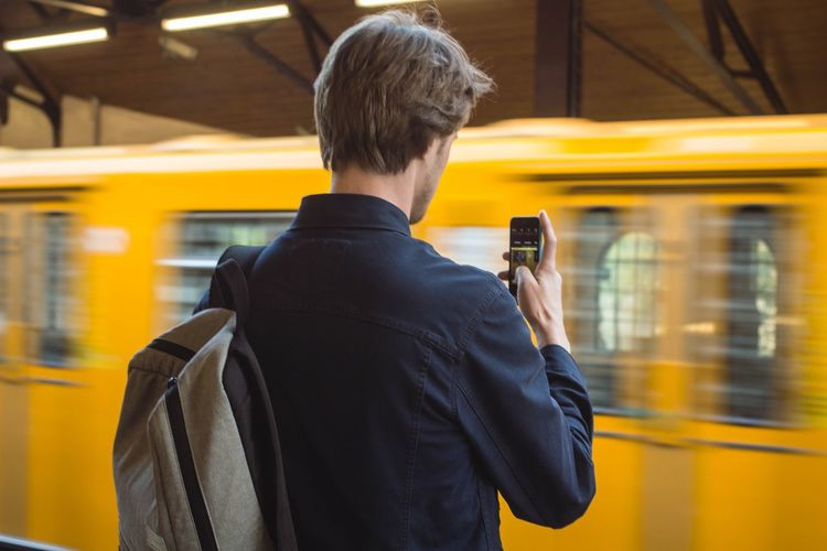 Rear view of man photographing blurred train at station