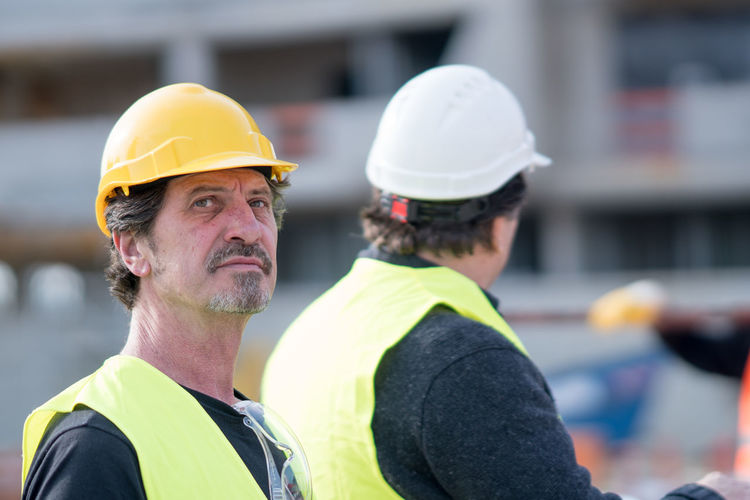 Engineer by colleague wearing hardhat at construction site