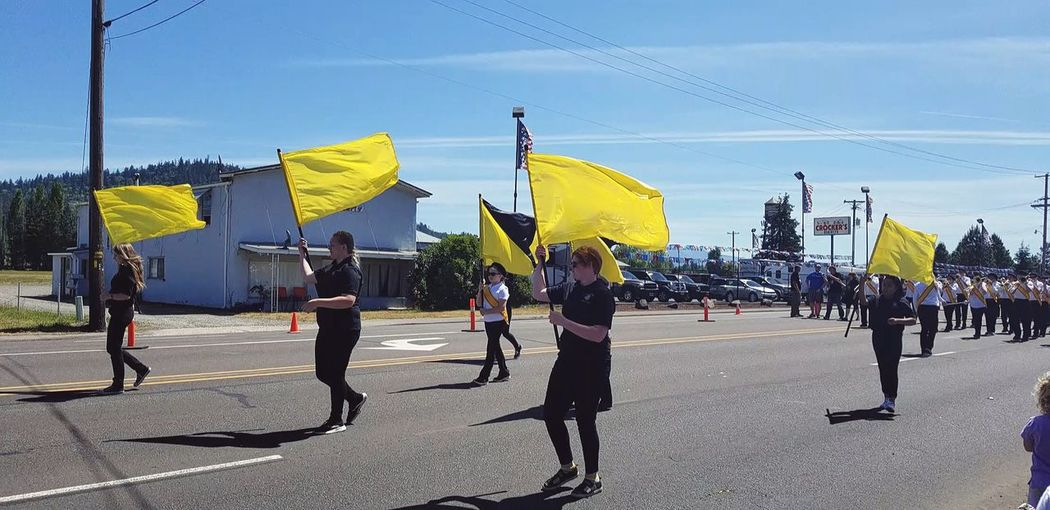 The 2018 Strawberry Parade in Oregon close to the Dutch Bros shop. Flags Yellow Flag Parade 2018 City Crowd Men Full Length City Life Sky Urban Scene Building Office Building Marching Band Pedestrian Street Scene City Street The Street Photographer - 2018 EyeEm Awards