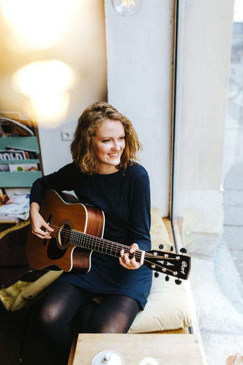 High angle view of smiling young woman playing guitar by window at home