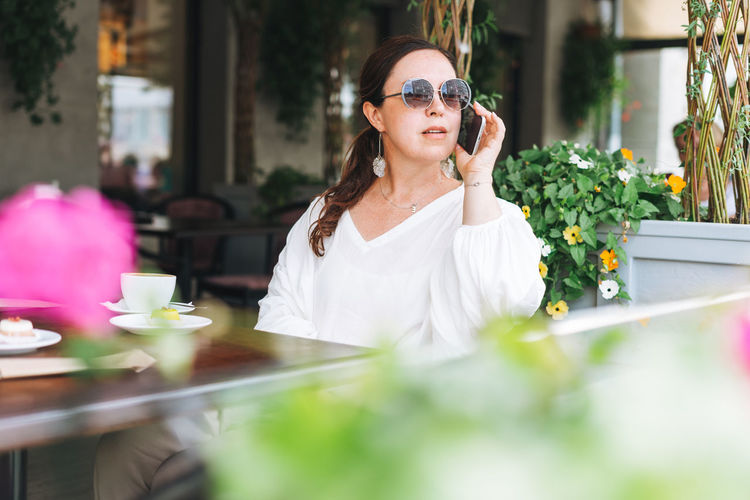 Portrait of young woman holding sunglasses at restaurant table
