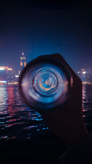 Person holding illuminated lighting equipment in sea against sky at night