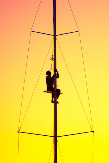 Low angle view of man sitting on mast against sky