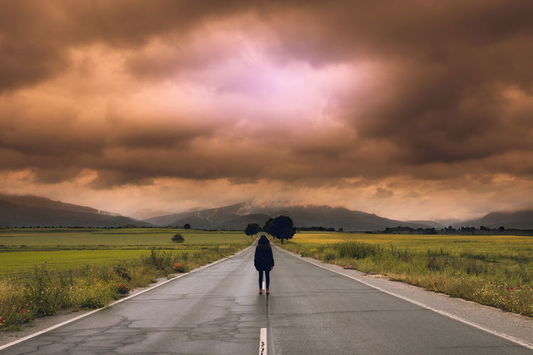 Rear view of person standing on road against cloudy sky