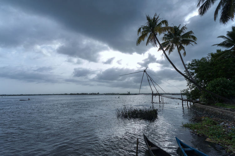 Kerala Backwaters on a Rainy Day Backwaters Backwaters Of Kerala Beauty In Nature Boats Chinese Fishing Nets Clouds Clouds And Sky Cloudy Coconut Trees Day India Kerala Kochi Lake Landscape Landscapes With WhiteWall Nature Outdoors Overcast Picturesque Rain Scenics Sky Tranquil Scene Water