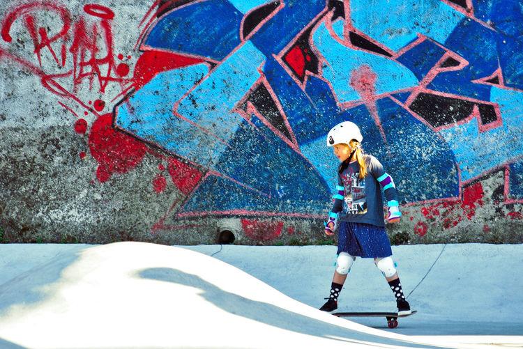 Girl skating against old graffiti wall