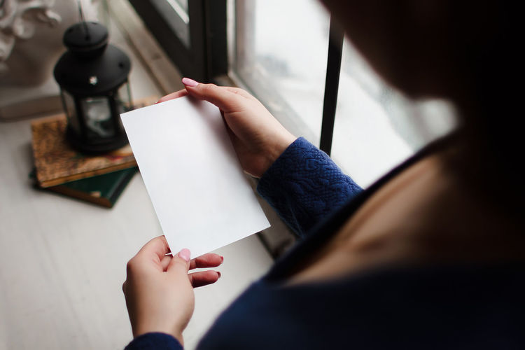 High angle view of woman hand holding paper
