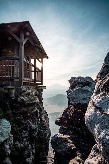 Hut on rock against sky