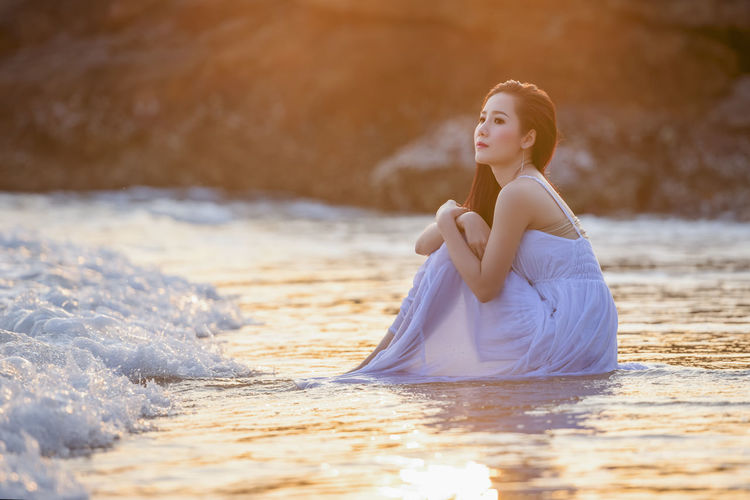 Young woman sitting on land in water
