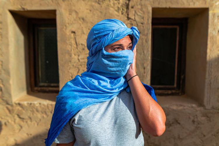 Woman wearing scarf looking away against windows