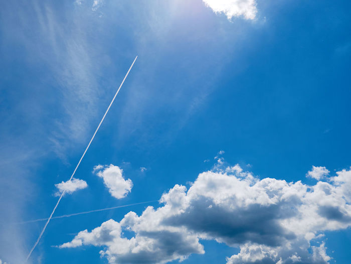 Cloud - Sky Sky Vapor Trail Low Angle View Beauty In Nature Blue Day Nature No People Tranquil Scene Tranquility Scenics - Nature Outdoors White Color Sunlight Air Vehicle Idyllic Transportation Heaven Cloudscape Meteorology
