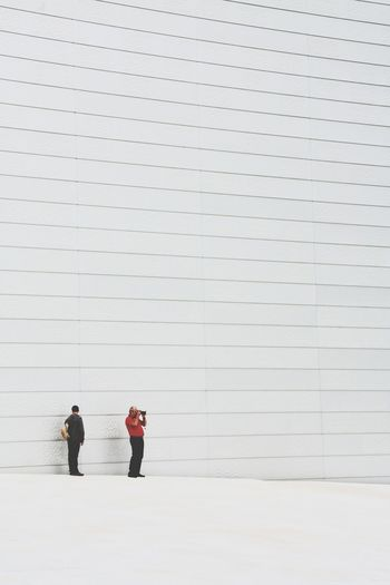Close-up of two men against white wall